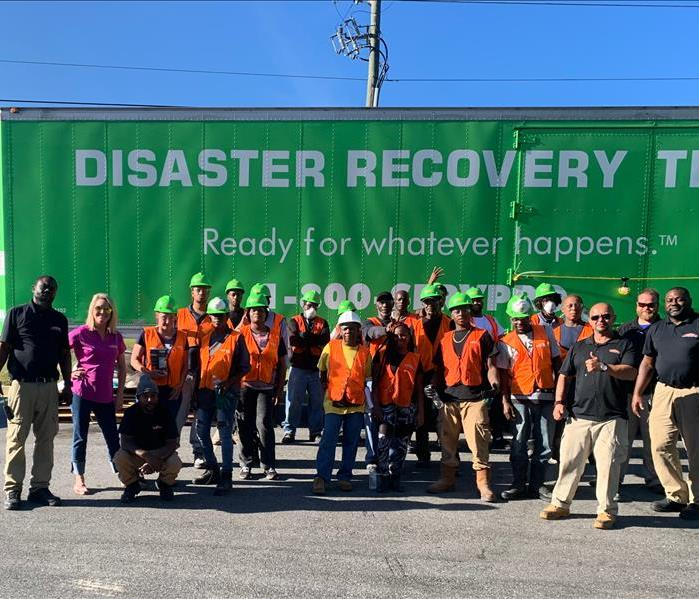 SERVPRO crew posing for pic in front of big rig